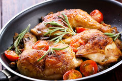 Roasted chicken. Legs with vegetable and herbs stock photos