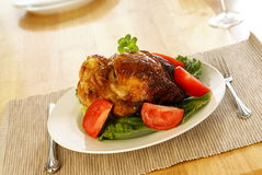 Roasted Chicken. Whole roasted chicken on bed of lettuce with tomatoe wedges Royalty Free Stock Photos