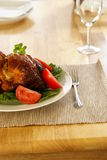 Roasted Chicken. Whole roasted chicken on bed of lettuce with tomatoe wedges Stock Images