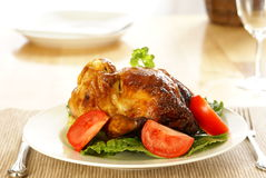 Roasted Chicken. Whole roasted chicken on bed of lettuce with tomatoe wedges Royalty Free Stock Images