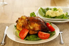 Roasted Chicken. Whole roasted chicken on bed of lettuce with tomatoe wedges. Mustard potato salad in the background Royalty Free Stock Photo