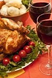 Roasted chicken. (turkey) garnished with tomatoes, potatoes and wine on holiday table ready to eat stock photo