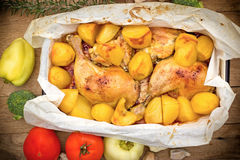 Roasted chicken and baked potatoes Stock Photography