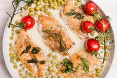 Roasted chicken breast in cream sauce with green pea and tomatoes Stock Images