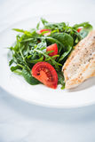 Roasted chicken breast and fresh salad with tomato and greens close up Royalty Free Stock Images