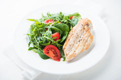 Roasted chicken breast and fresh salad with tomato and greens close up Stock Image