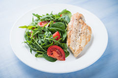 Roasted chicken breast and fresh salad with tomato and greens (spinach, arugula) close up on blue wooden background Royalty Free Stock Photos
