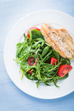 Roasted chicken breast and fresh salad with tomato and greens (spinach, arugula) top view on blue wooden background Royalty Free Stock Photo
