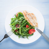 Roasted chicken breast and fresh salad with tomato and greens (spinach, arugula) top view on blue wooden background Royalty Free Stock Images
