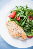 Roasted chicken breast and fresh salad with tomato and greens (spinach, arugula) top view on blue wooden background Royalty Free Stock Image