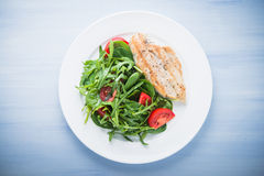 Roasted chicken breast and fresh salad with tomato and greens (spinach, arugula) top view on blue wooden background Stock Photo