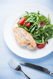 Roasted chicken breast and fresh salad with tomato and greens (spinach, arugula) top view on blue wooden background Stock Images