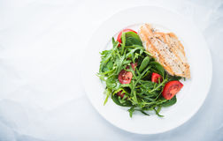 Roasted chicken breast and fresh salad with tomato and greens top view Stock Photo