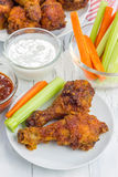 Roasted chicken with celery and carrot sticks, blue cheese dressing and hot sauce Stock Photo