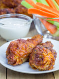 Roasted chicken with celery and carrot sticks, blue cheese dressing and hot sauce Stock Photos