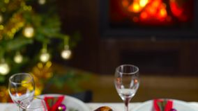Roasted chicken on christmas table in front of fireplace and tree with lights. Roasted chicken with apples on christmas table in front of fireplace and christmas stock video footage