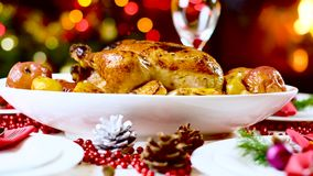 Roasted chicken on christmas table in front of fireplace and tree with lights. Roasted chicken with apples on christmas table in front of fireplace and christmas stock footage