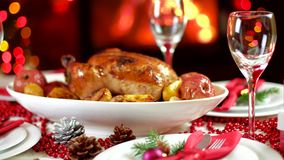 Roasted chicken on christmas table in front of fireplace and tree with lights. Roasted chicken with apples on christmas table in front of fireplace and christmas stock video