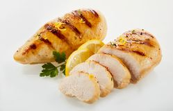 Roasted chicken cut in slices with lemon royalty free stock photography