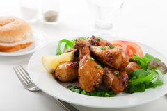 Roasted chicken drumsticks. And salad on white plate Stock Photo