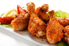 Roasted chicken drumsticks. Roasted chicken legs and vegetables stock photos