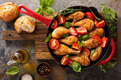 Roasted chicken drumsticks in a cast iron pan. With tomatoes and basil Stock Photo