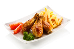 Roasted chicken drumsticks with chips Stock Photos