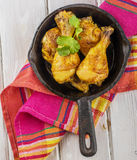 Roasted chicken drumsticks in  pan on a wooden Stock Photo