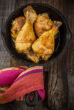 Roasted chicken drumsticks in  pan on a wooden Stock Photography