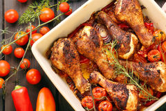 Roasted chicken drumsticks with vegetables in a pan Stock Photos