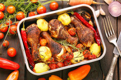 Roasted chicken drumsticks with vegetables in a pan Stock Photo