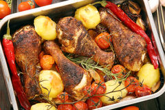 Roasted chicken drumsticks with vegetables in a pan Stock Image