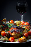 Roasted chicken with fried potatoes and cherry tomatoes. Roasted chicken with fried potatoes and cherry tomatoes on black background Stock Photography