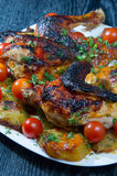Roasted chicken with fried potatoes and cherry tomatoes. Roasted chicken with fried potatoes and cherry tomatoes on white plate Royalty Free Stock Photo