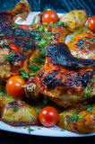 Roasted chicken with fried potatoes and cherry tomatoes. Roasted chicken with fried potatoes and cherry tomatoes on white plate Royalty Free Stock Image