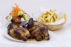 Roasted chicken with fries potato called Pollo a la Brasa. Menu served with fresh salad and french fries Royalty Free Stock Images