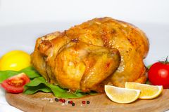 Roasted chicken with a golden crust with lemon and vegetables. On a wooden board Royalty Free Stock Images