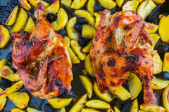 Roasted chicken halves, black baking sheet, potatoes and olives, cooked in oil, top view.  stock photography