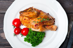 Roasted Chicken. With herbs and tomatoes on the plate over wooden background stock photo