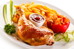 Roasted chicken leg with chips. Roasted chicken leg and vegetables stock photo