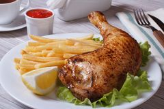 Roasted chicken leg with french fries, lemon and ketchup Stock Photo