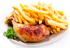 Roasted chicken leg with fries potato stock images