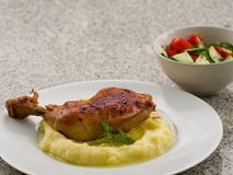 Roasted chicken leg marinated in the honey, paprika and garlic with mashed potatoes as a side dish and butter. Royalty Free Stock Image