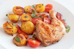 Roasted chicken leg with potato, pumpkin, and cherry tomatoes decorated with cilantro and pumpkin seeds Stock Image