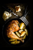Roasted chicken leg with potatoes Stock Images