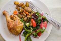 Roasted chicken leg, potatoes and vegetable salad Royalty Free Stock Image