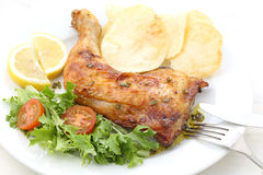 Roasted chicken leg with salad and chips on a table Royalty Free Stock Photos