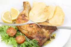 Roasted chicken leg-top view with fork and knife Royalty Free Stock Photography