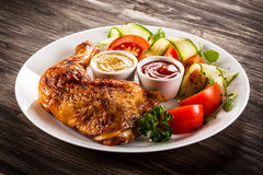 Roasted chicken leg. With vegetables stock photos