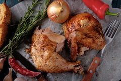 Roasted chicken leg and wing with chili on a wooden table Royalty Free Stock Photos